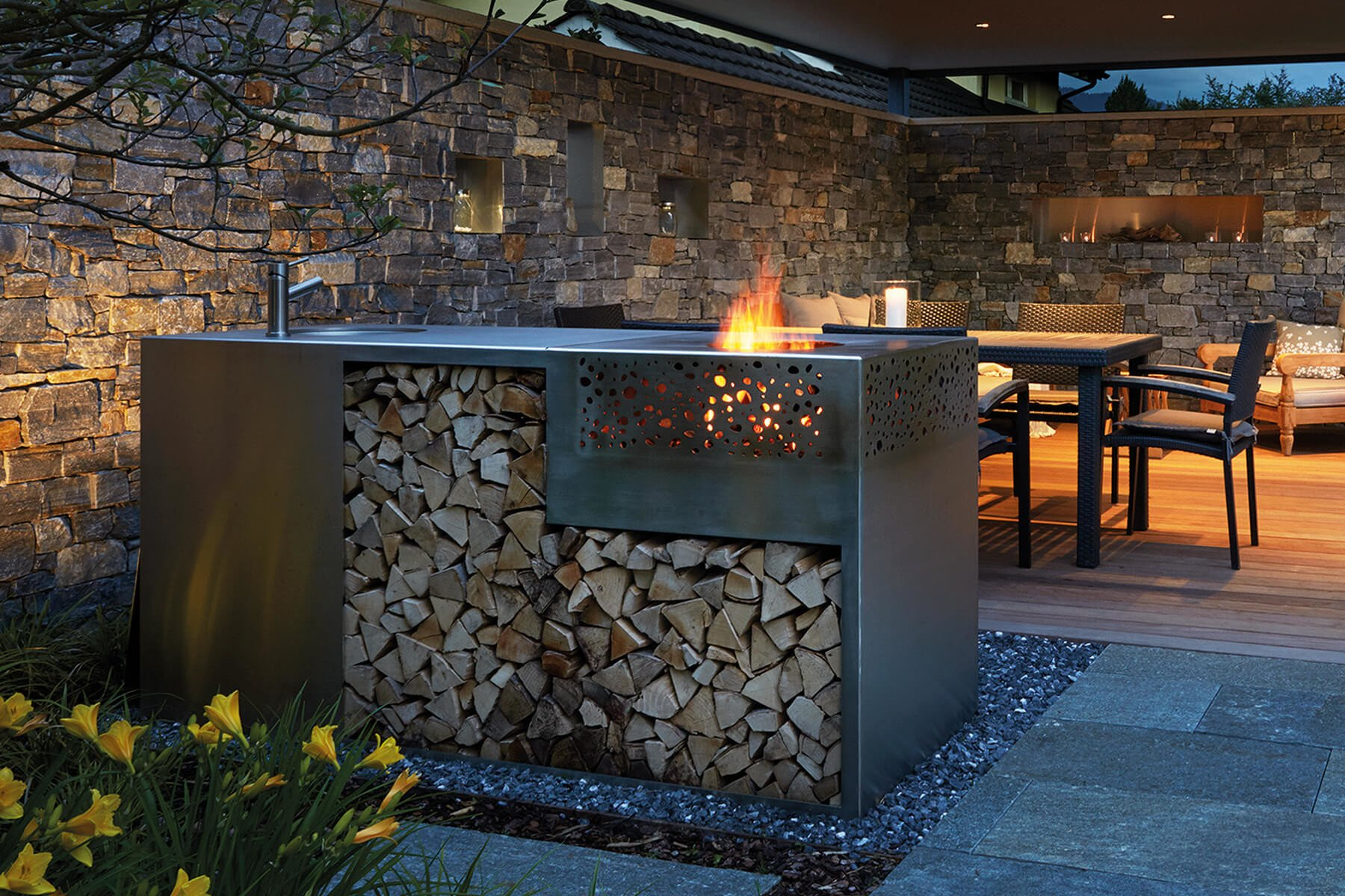 Flammengrill aus Edelstahl beschichtet mit integriertem Holzdepot abends im Garten