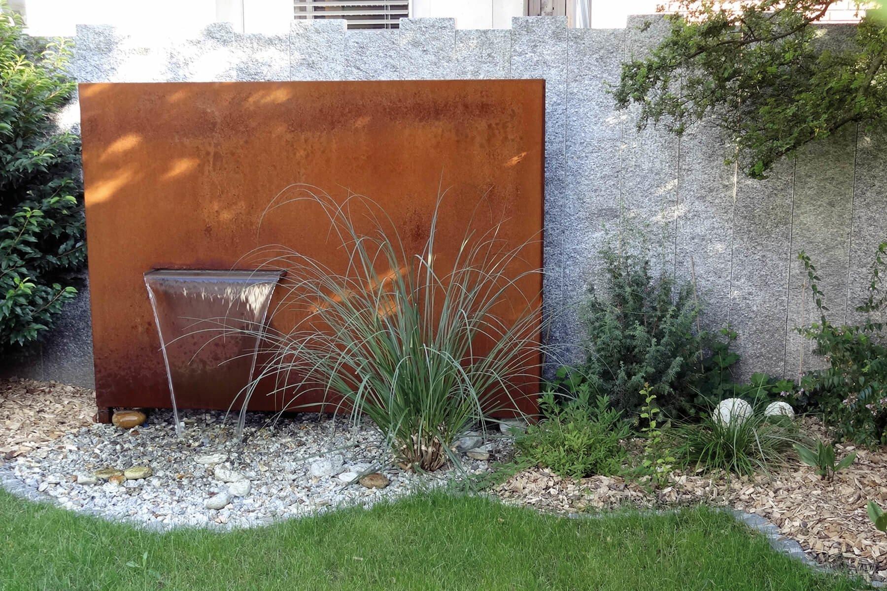 Wasserbrunnen aus Cortenstahl an Gartenmauer