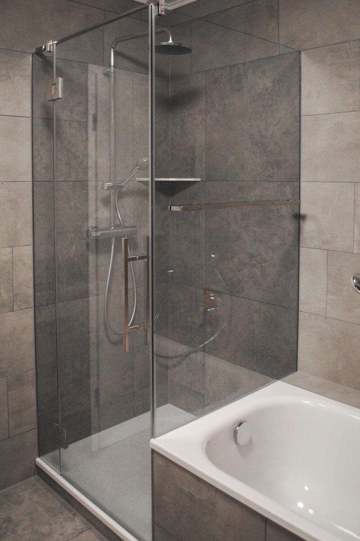Duschkabine an Wanne mit zwei Festteilen und großen geschlossenen Tür