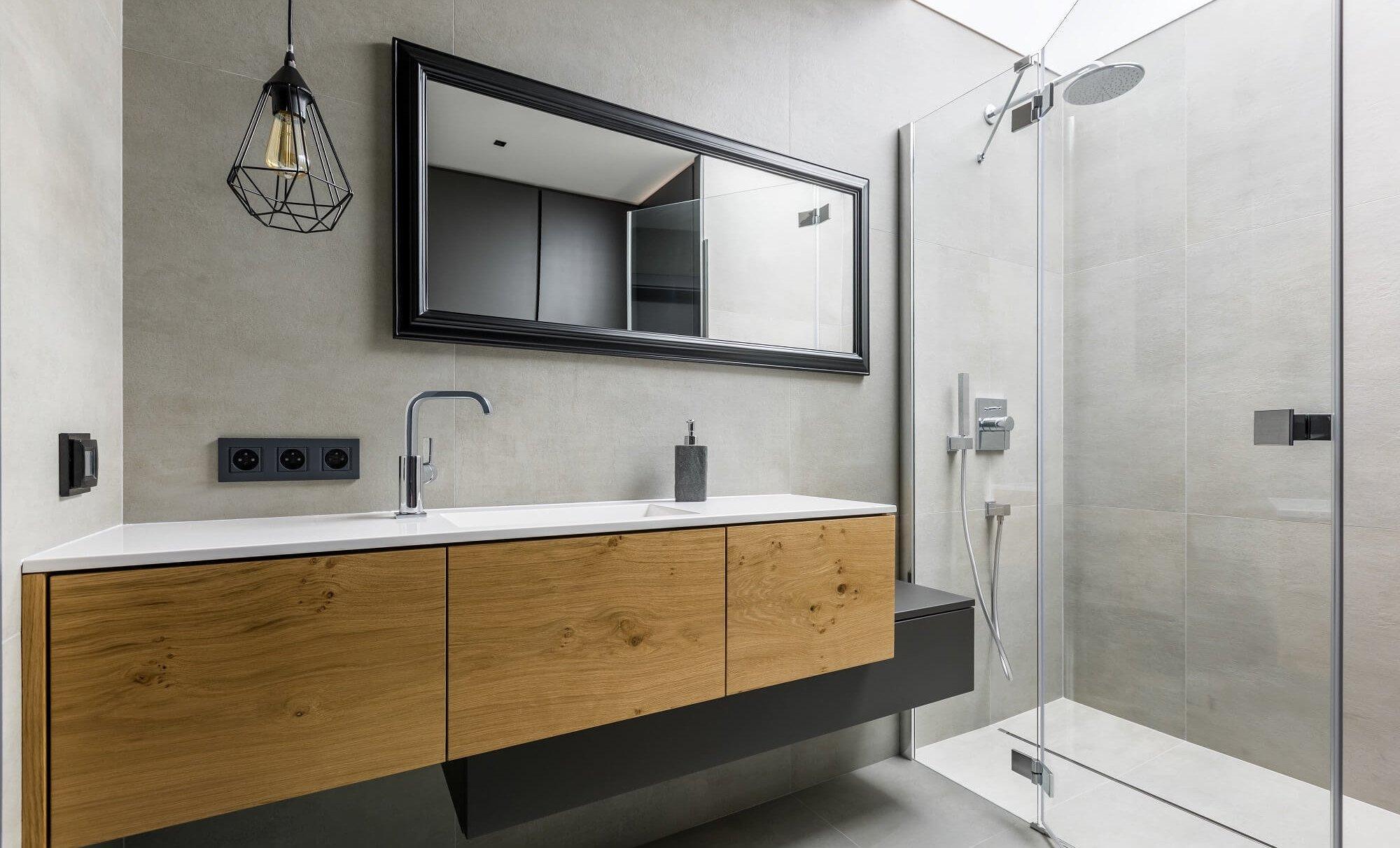 modernes_Badezimmer_mit_grauen_Fliesen_und_einer_Dusche_aus_Glas