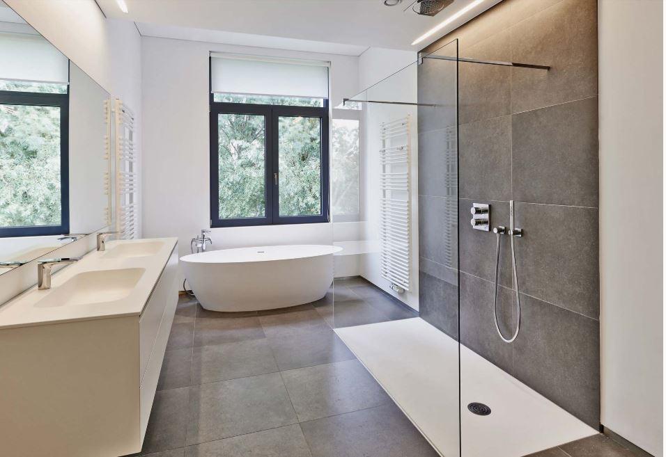 grosse_barrierefreie_walk_in_dusche_aus_glas_im_modernen_badezimmer_mit_freistehender_badewanne