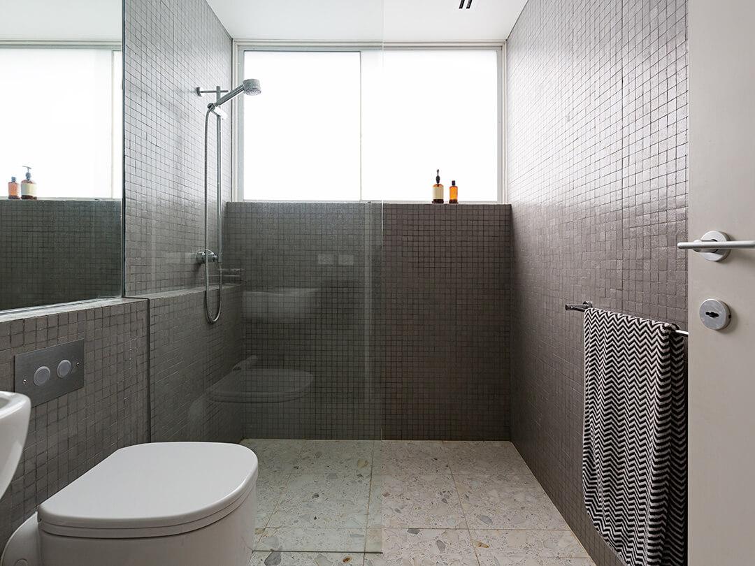 Walk-in-Dusche bodeneben mit einem Glaselement an der Wand befestigt