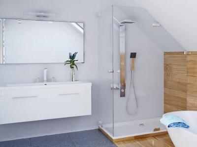 Eckdusche mit einer Tür unter Schräge neben Waschbecken im Bad