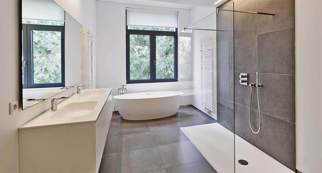 grosse_barrierefreie_walk_in_dusche_aus_glas_im_modernen_badezimmer_mit_freistehener_badewanne