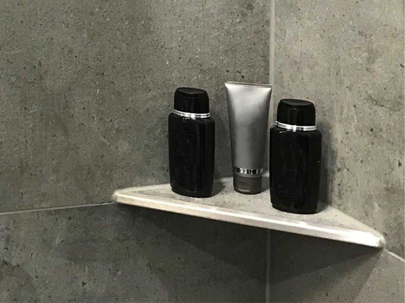 Duschablage aus massivem Edelstahl in einer Ecke mit Shampooflaschen