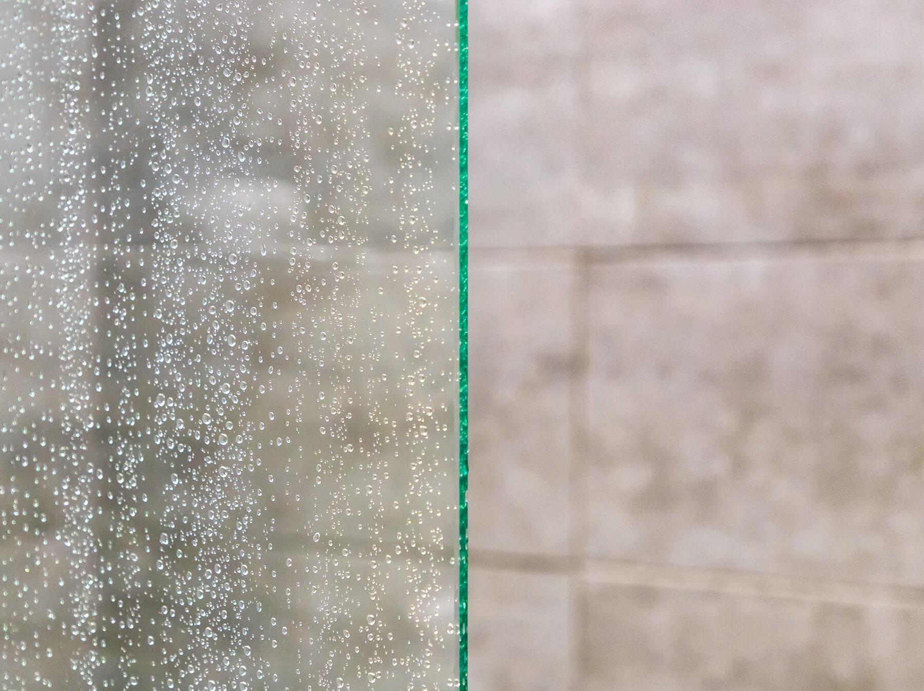 Feine Wassertropfen auf Glasscheibe im Badezimmer