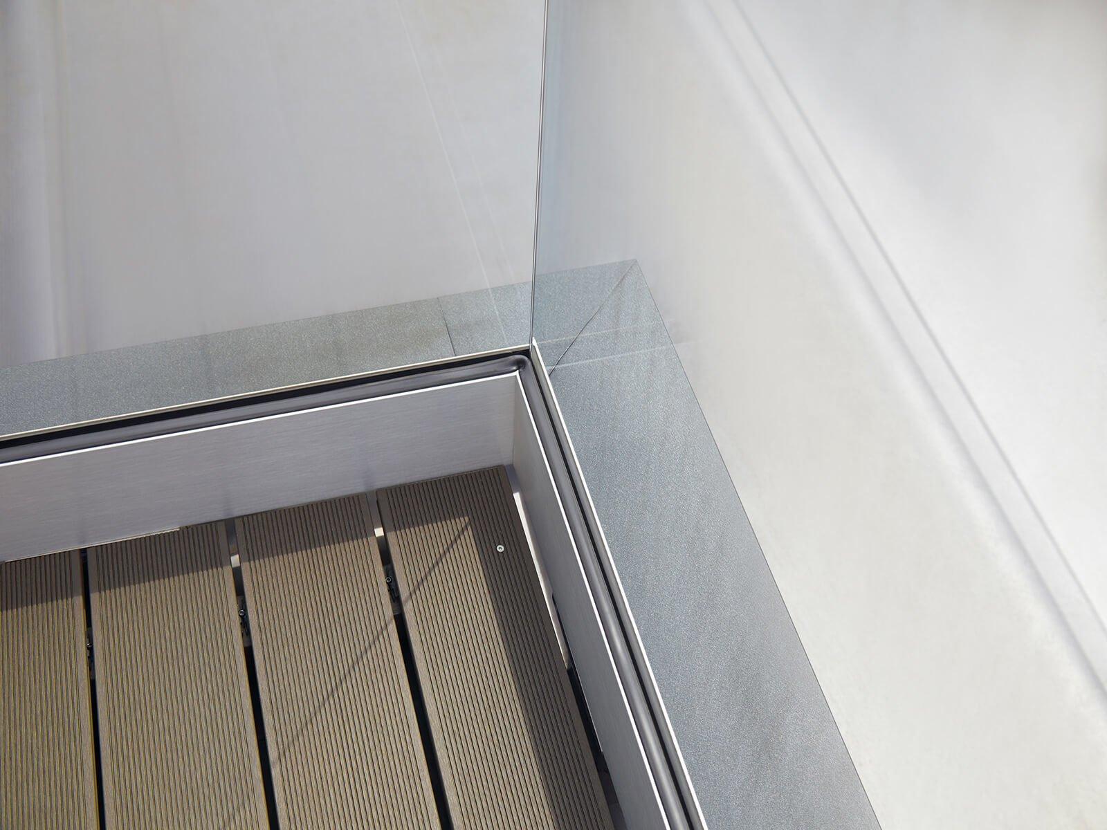 Glasrailing FORMAL auf einem Balkon mit Abkantblech zum Schutz der Dämmung