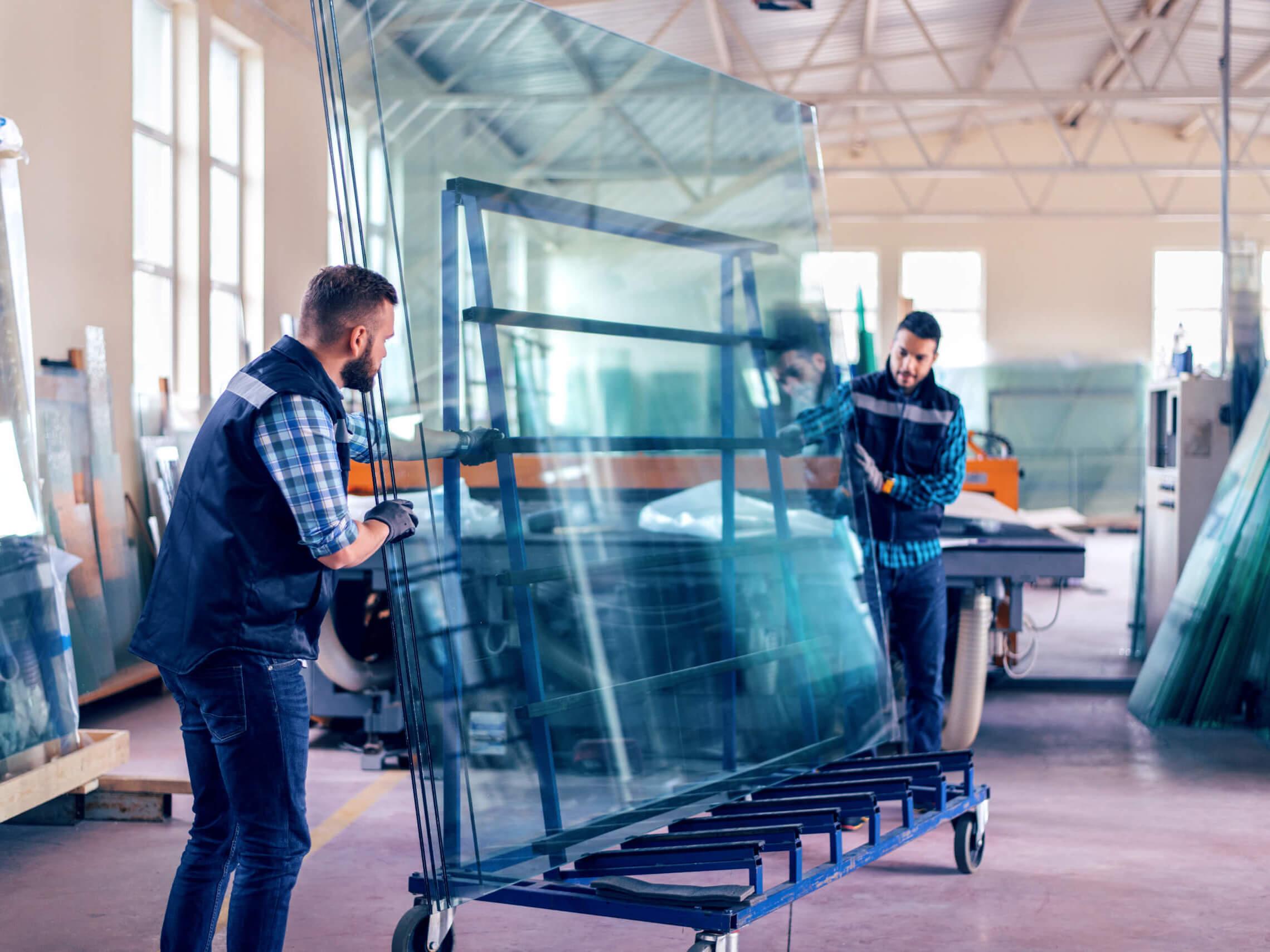 wand-glas-wird-im-lager-von-zwei-mitarbeitern-transportiert