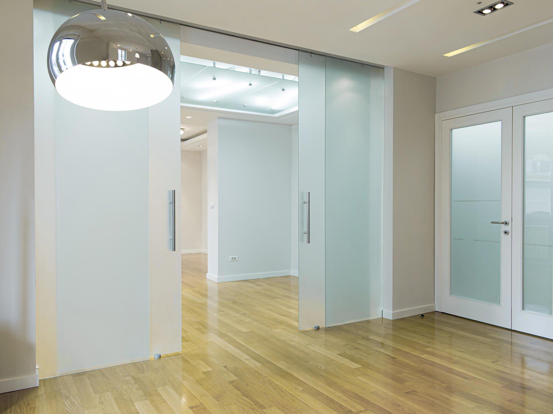 Glastrennwand mit Schiebetür und satiniertem Glas als Sichtschutz im Büro