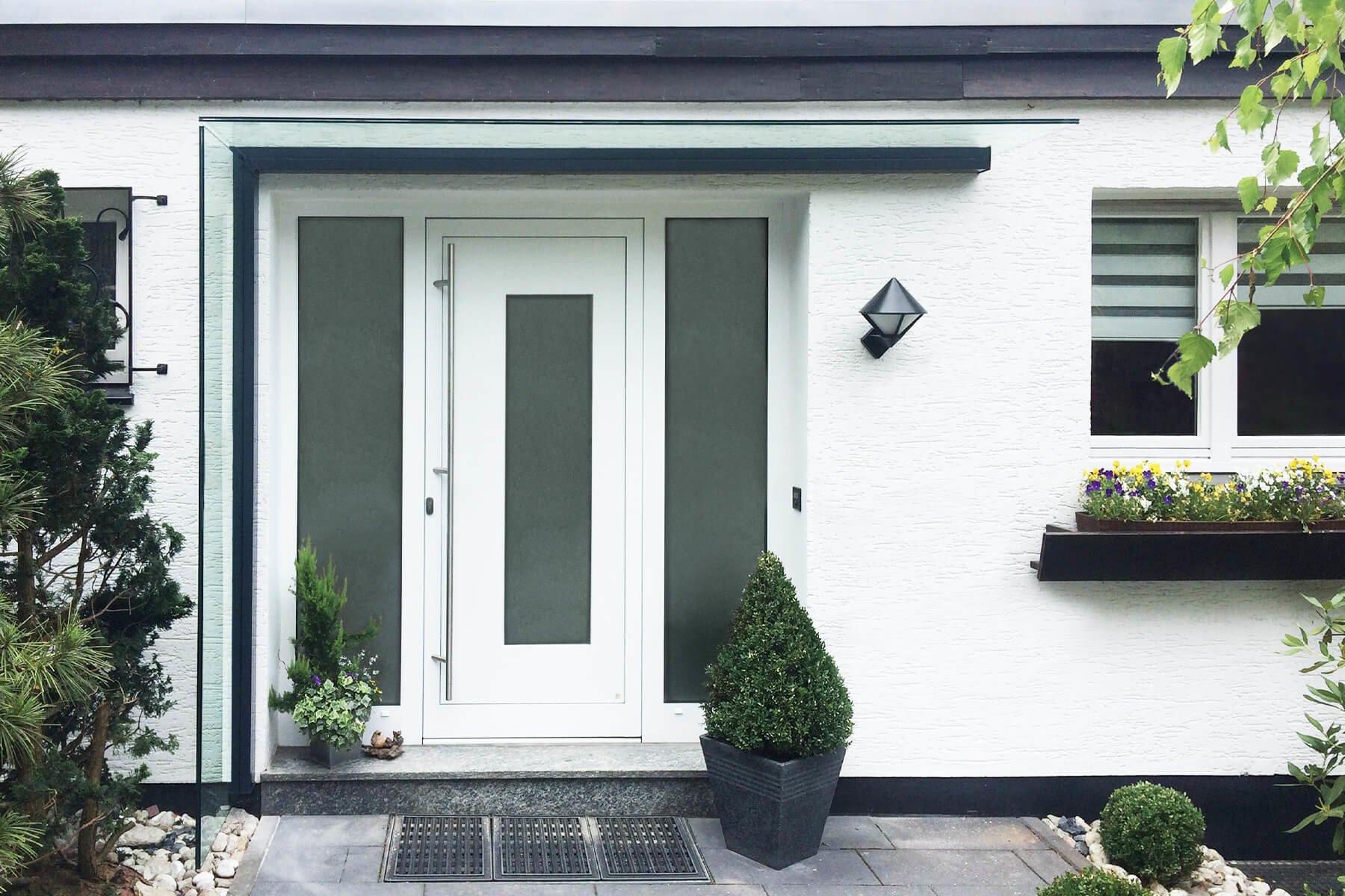 vordach-mit-seitenteil-aus-klarglas-an-weißer-fassade