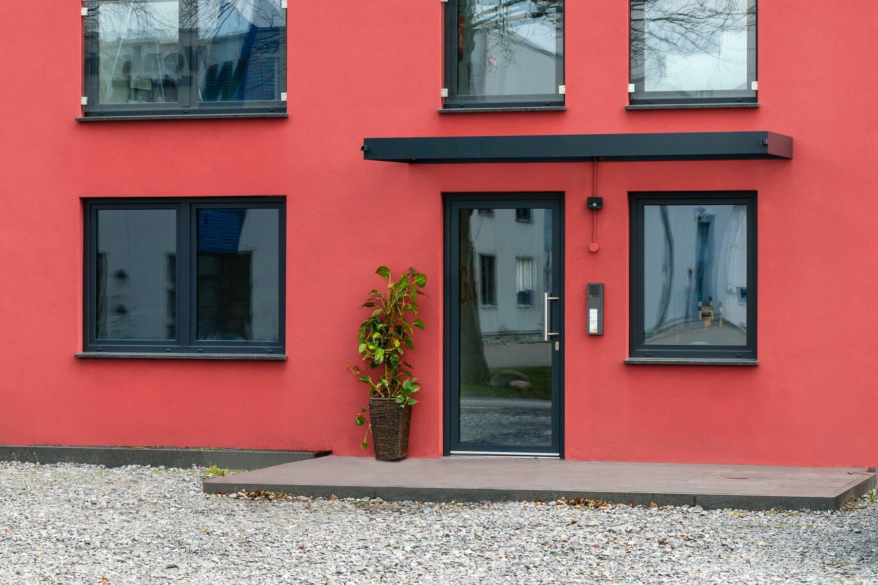Hochwertiges Vordach an roter Fassade