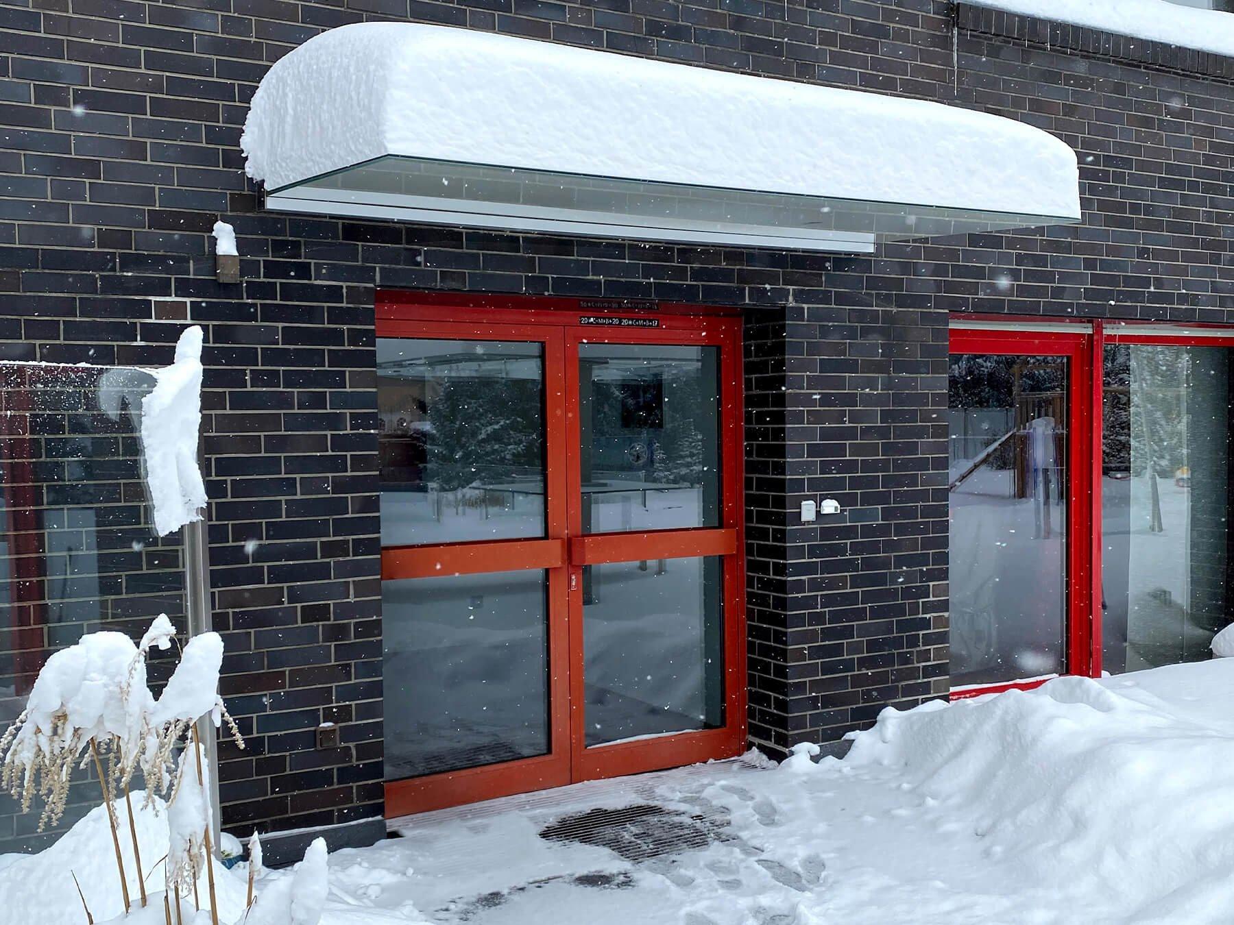 Freitragendes Glasvordach mit Schnee bedeckt vor Hauseingang