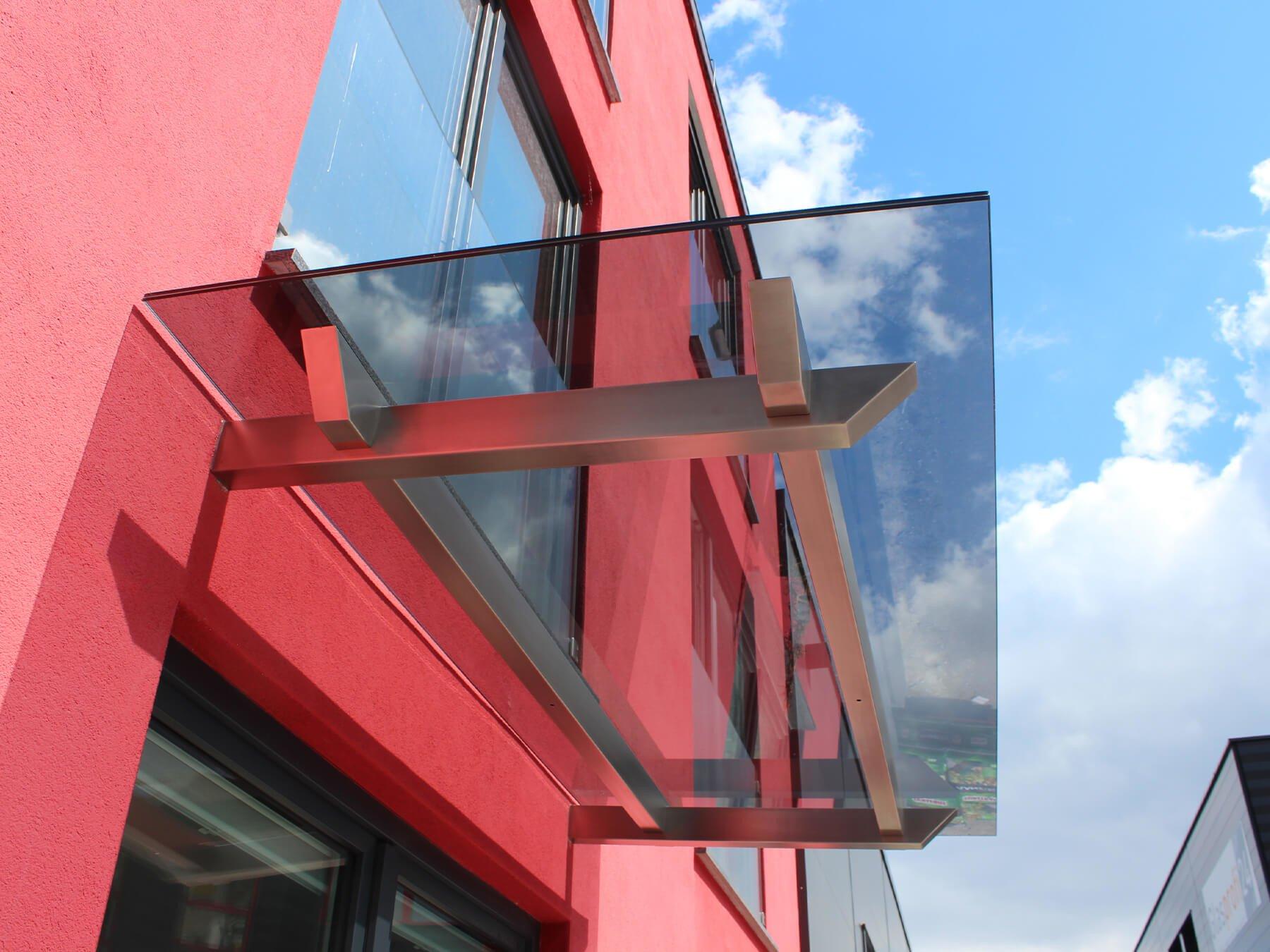 Glasvordach mit Balkenträgern aus Edelstahl in markantem Design