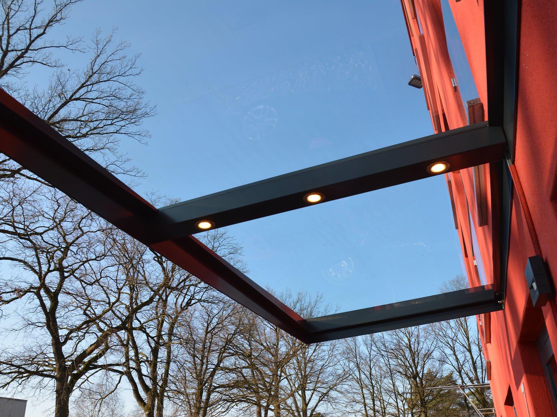 Großes Glasvordach mit umlaufendem Stahlrahmen in schwarz und integrierten Spots