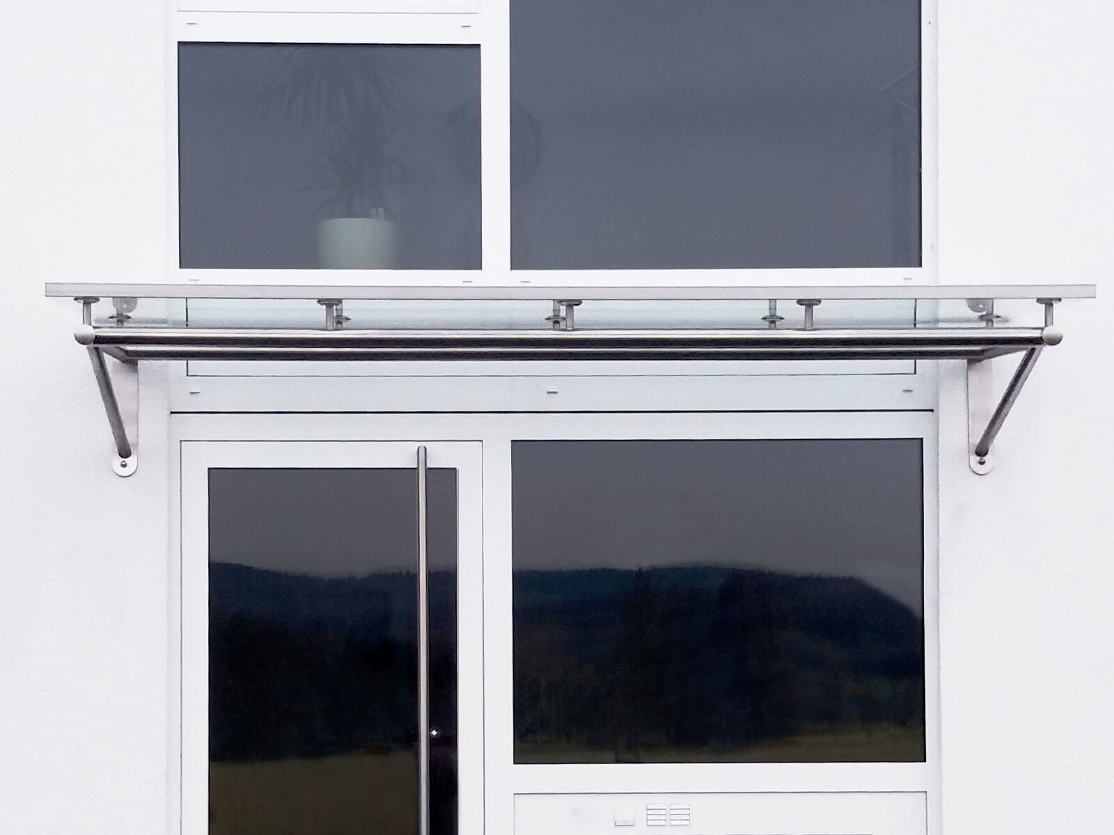 Glas Vordach Trave an Wärmedämmfassade