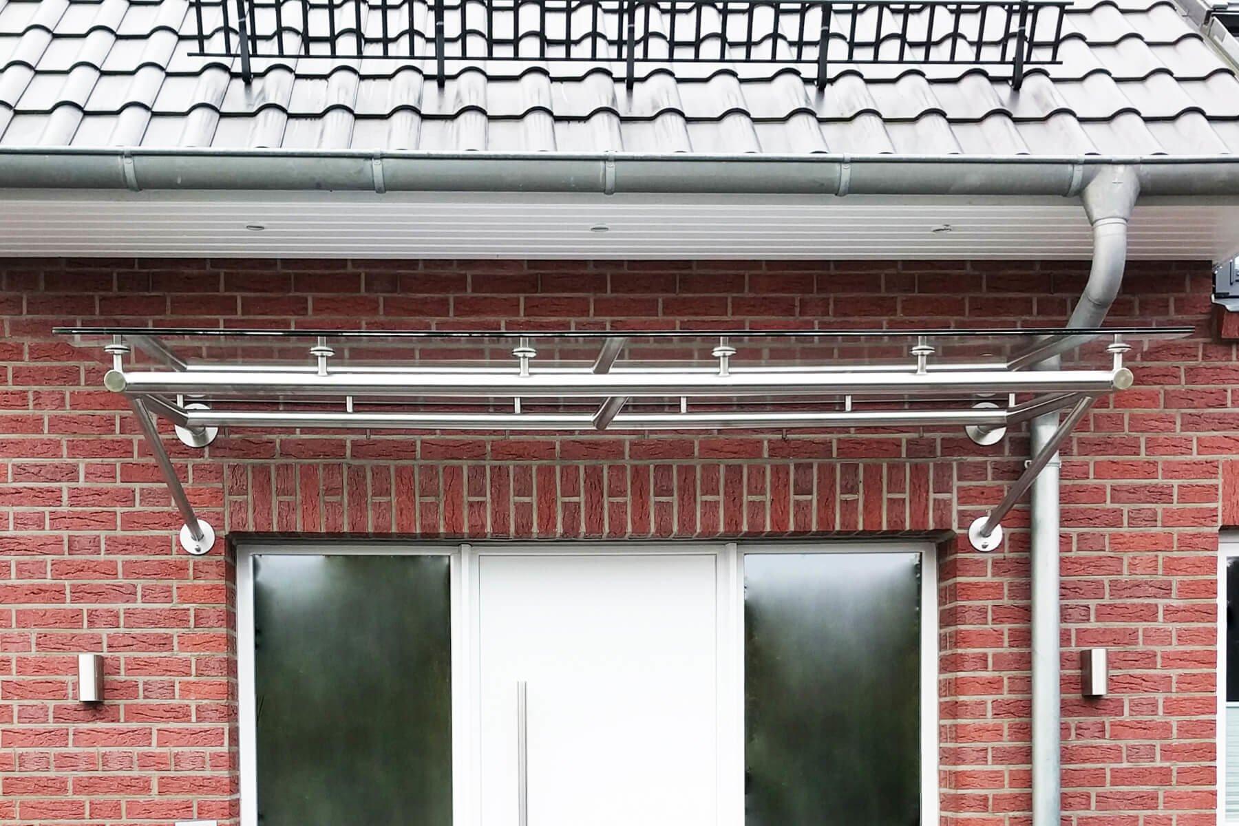 Rohrrahmen Glas Vordach an Klinker Fassade