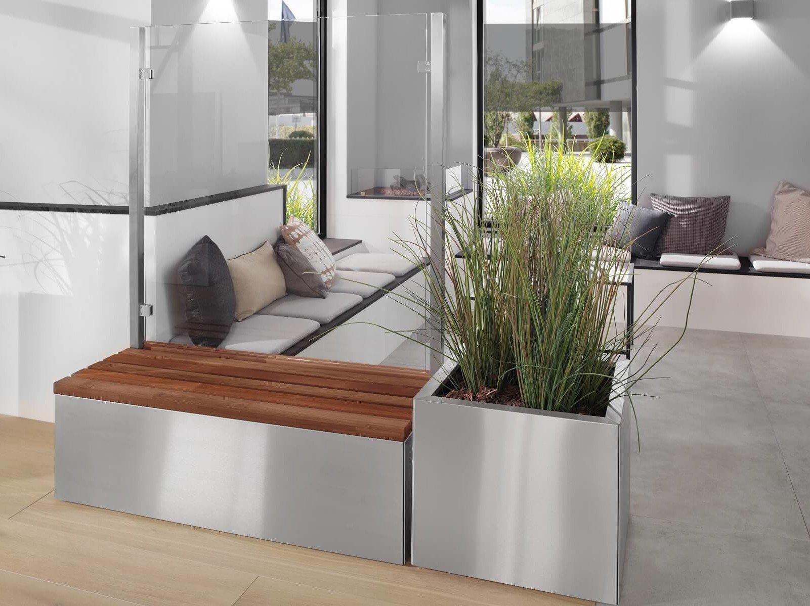 Glastrennwand mit Bank und Pflanzkübel aus Edelstahl nebeneinander in der Hotelloby