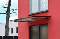 Design Vordach Skala an roter Fassade