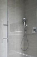 Dusche aus Glas mit Griffstange und Duschkopf