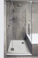 Duschkabine neben Badewanne mit zwei Festteilen und Tür