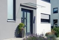 glasvordach-freitragend-an-grauer-fassade