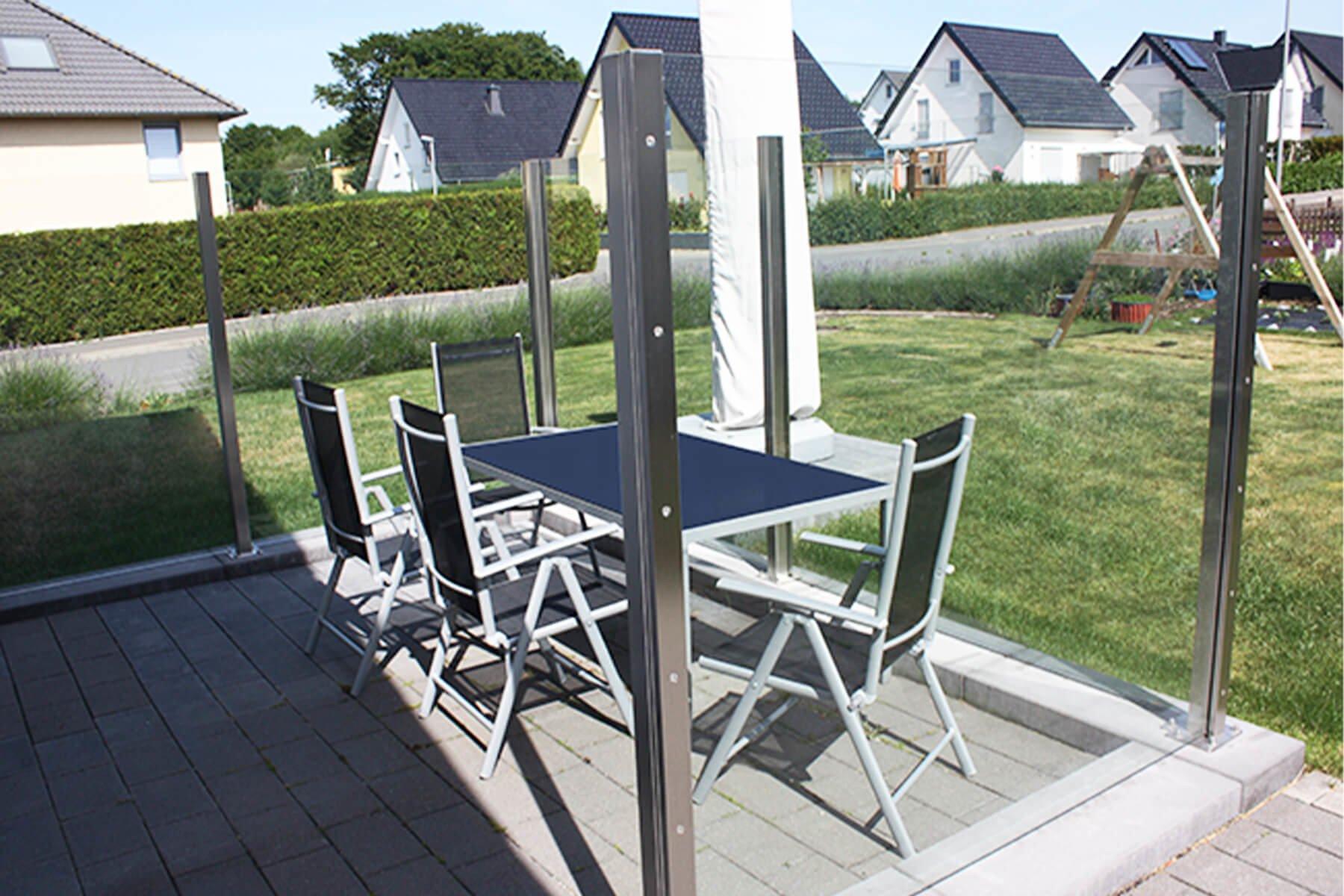 Durchgehend geschlossener Windschutz aus Glas in moderner Optik für Garten und Terasse
