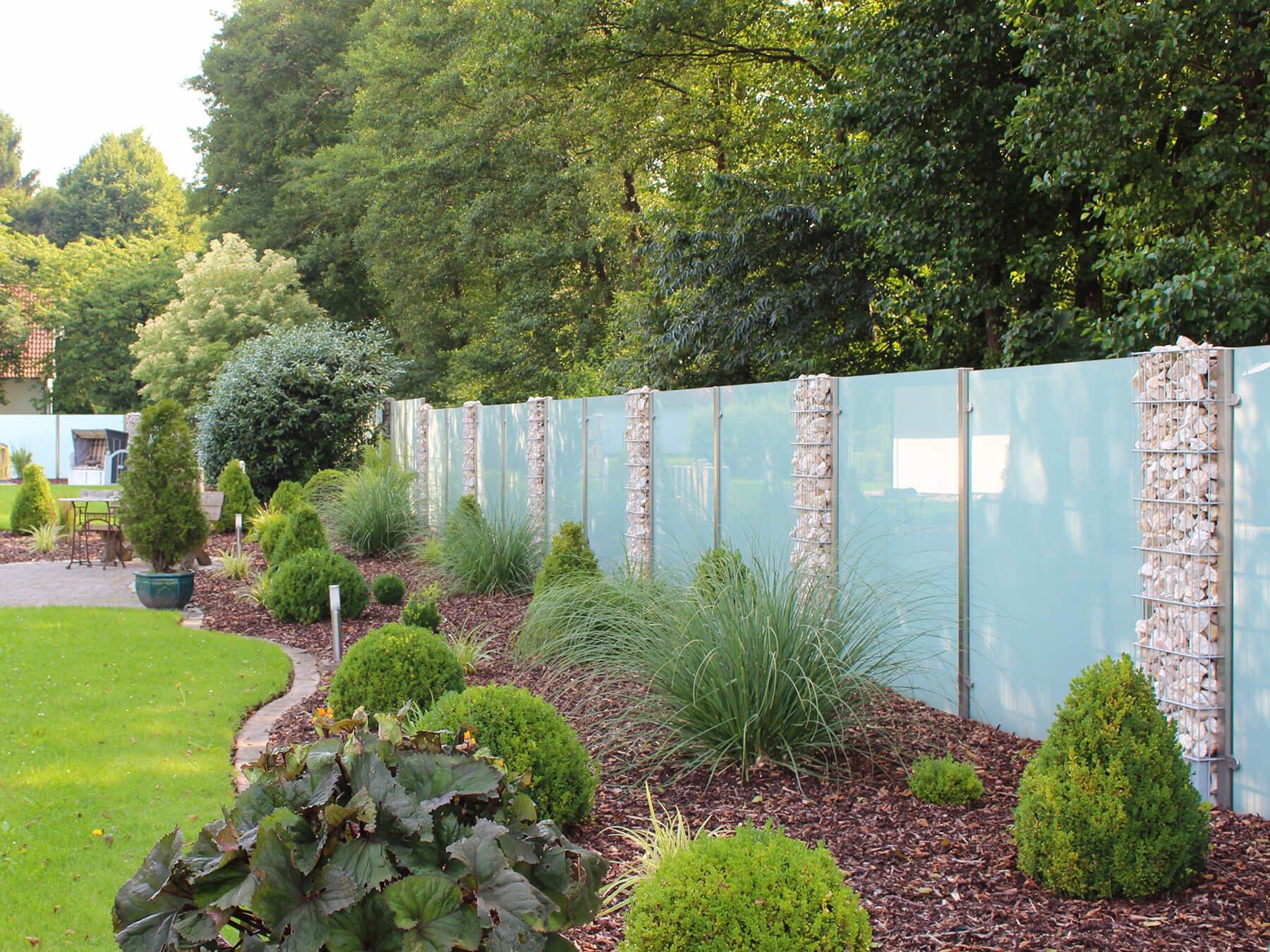 Wind- und Sichtschutz eckig mit seitlichen Glasklemmen kombiniert mit Gabionenzaun